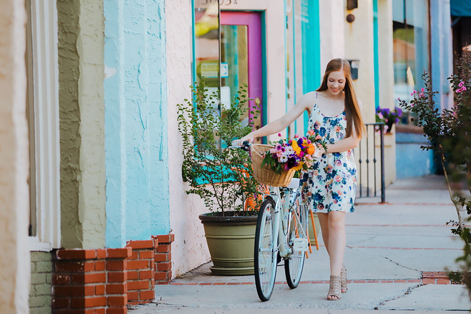 Senior girl with long red hair, pushing a bike with flowers in the bakers in the Paseo District in Oklahoma City by Amanda Lynn.