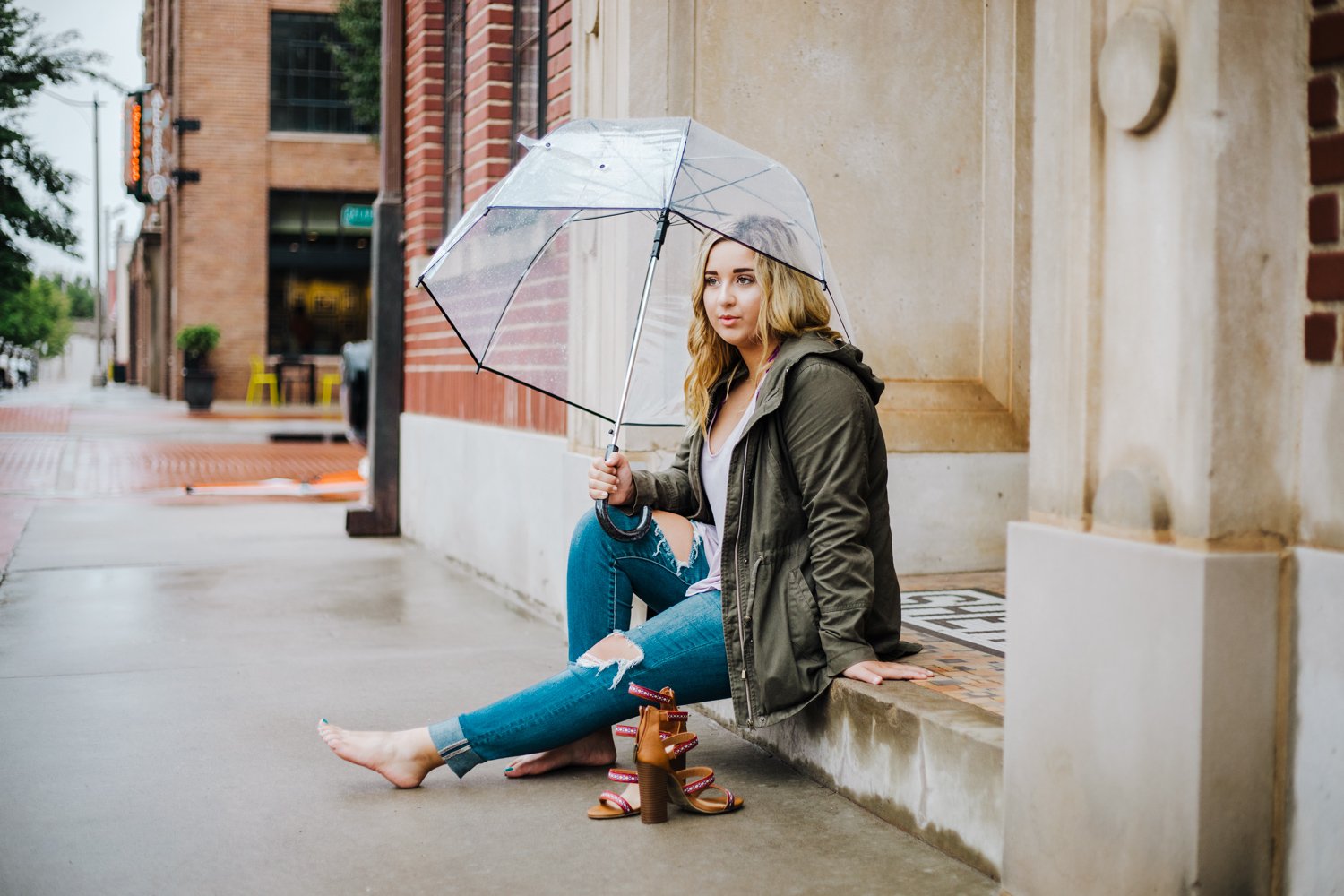 Oklahoma Senior girl sitting on step holding a clear umbrella in downtown Oklahoma City by Amanda Lynn Photography.