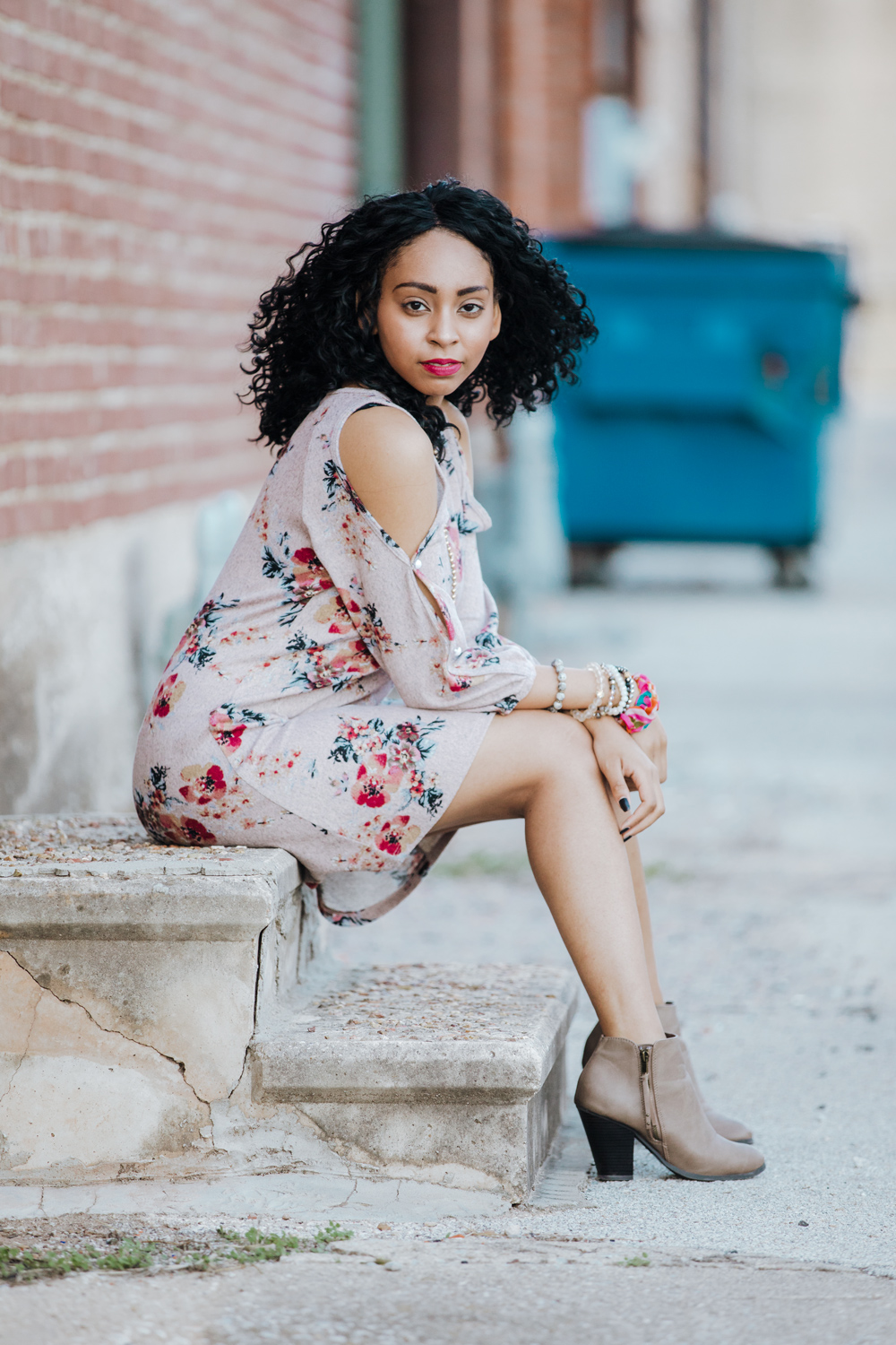High school senior girl wearing floral dress and heels, sitting on stairs in downtown Shawnee.