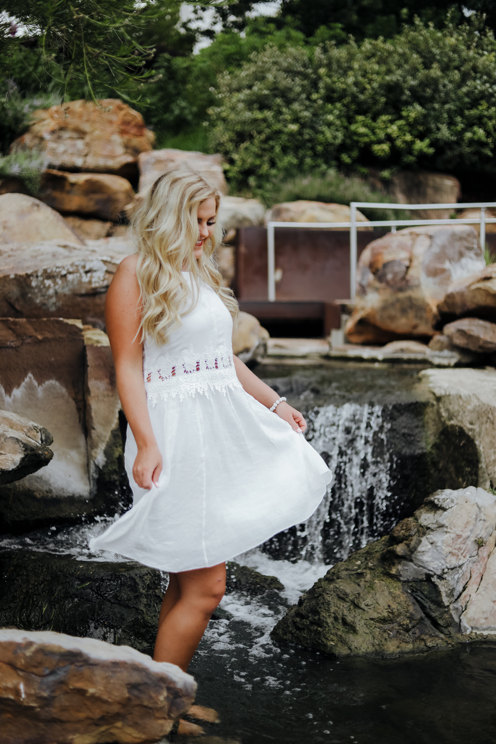 High school senior girl wearing white summer dress, dancing in a fountain at the Myriad Gardens in OKC.