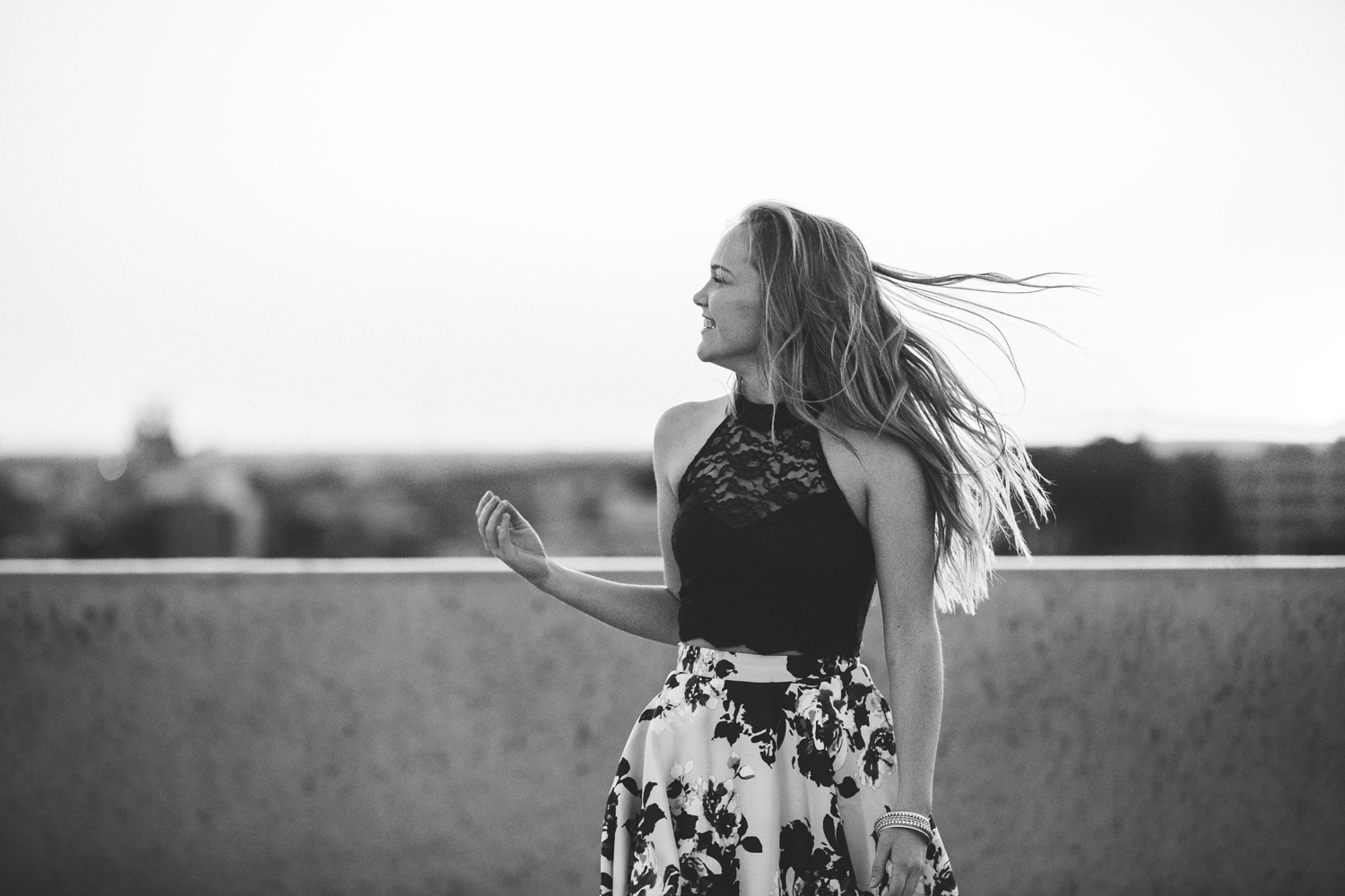 Black and white image of high school senior girl laughing while her hair blows in the wind on a rooftop in automobile alley, Oklahoma City.