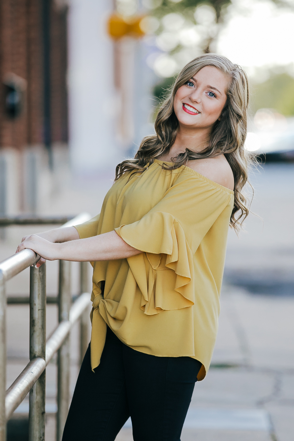 Oklahoma high school senior girl wearing black pants and yellow top, holding onto stair rail in automobile alley in downtown OKC by Amanda Lynn Photography.