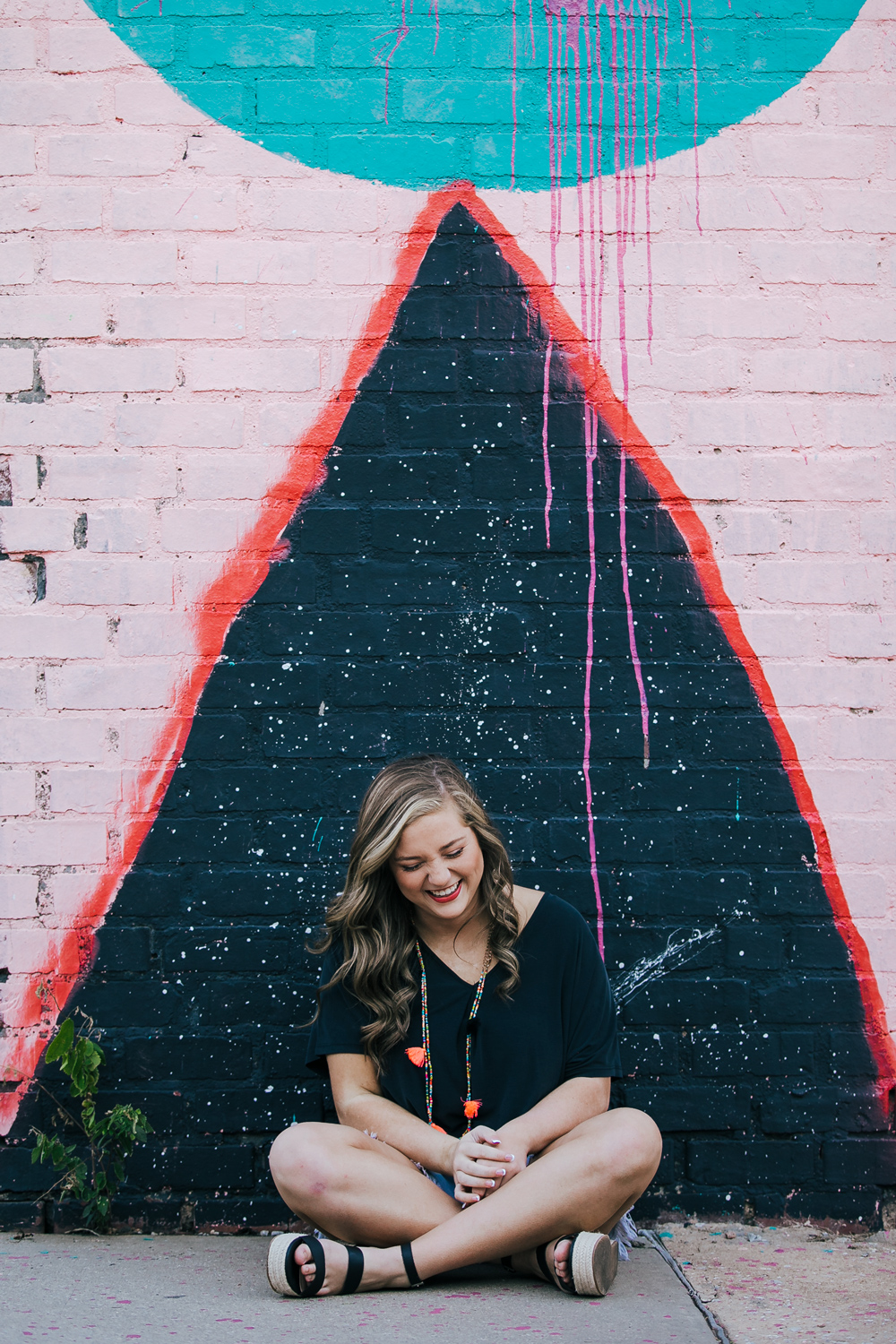 High school senior girl wearing shorts and black top, sitting in front of a triangle painted on a brick building in automobile alley, okc.