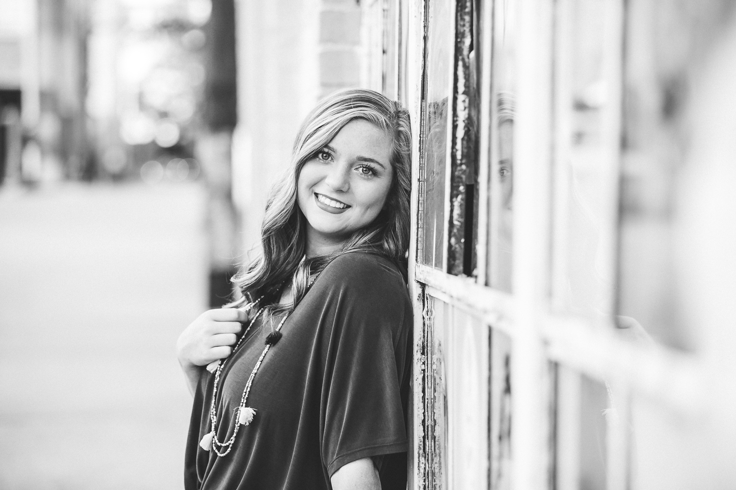 Black and white image of high school senior girl leaning against windows in automobile alley by amanda lynn photography oklahoma.