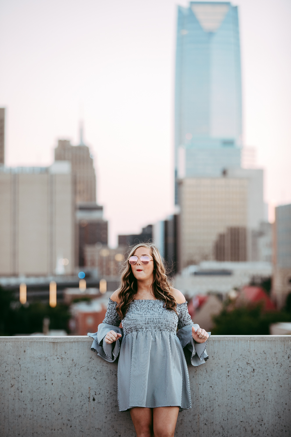 High school senior girl leaning against concrete wall with downtown OKC in the background by Amanda Lynn Photography.