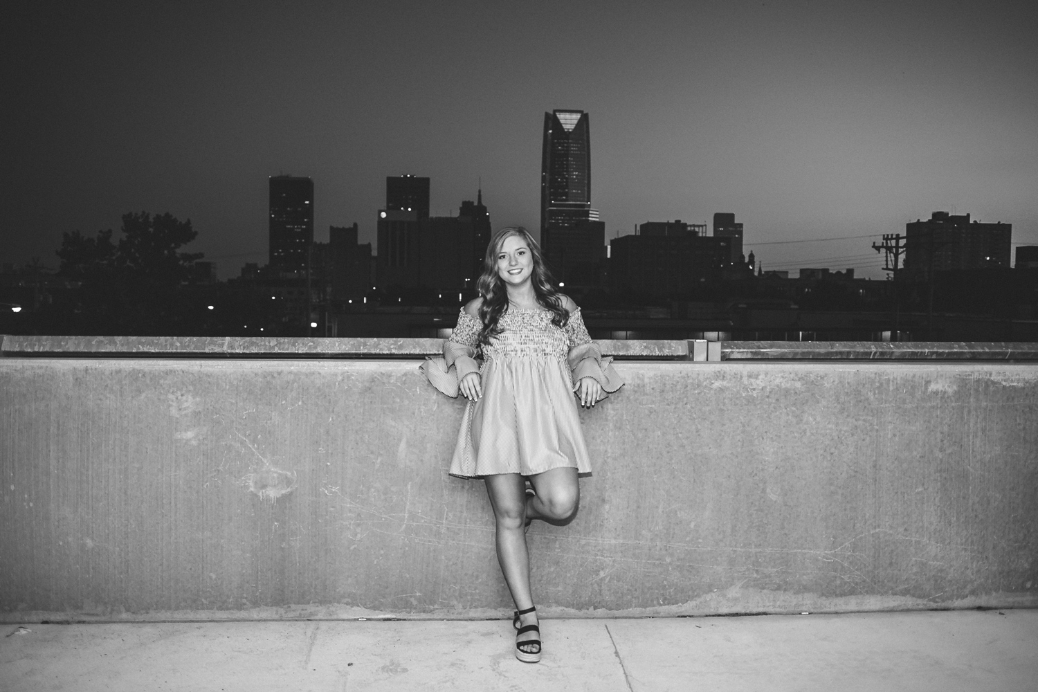 Black and white night image of high school senior leaning against a half concrete wall with downtown OKC in the background.