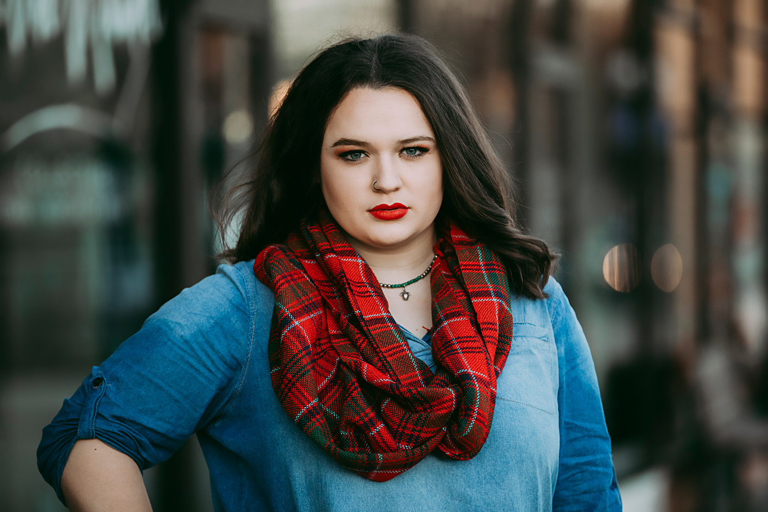 High School senior girl with long brown hair, wearing red scarf looking at camera in the Plaza District in OKC by Amanda Lynn.