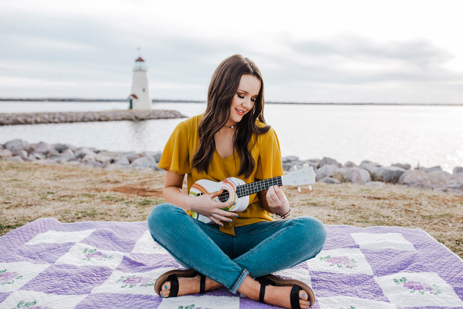 High school senior girl wearing jeans and a yellow top, sitting on quilt and playing the ukulele with the Oklahoma City Lighthouse behind her at Lake Hefner by Amanda Lynn Photography.