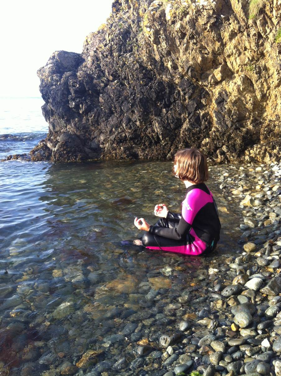Here is one of our little yoginis practicing her cloud meditation in Wales. Apparently a seal was watching her as she practised.