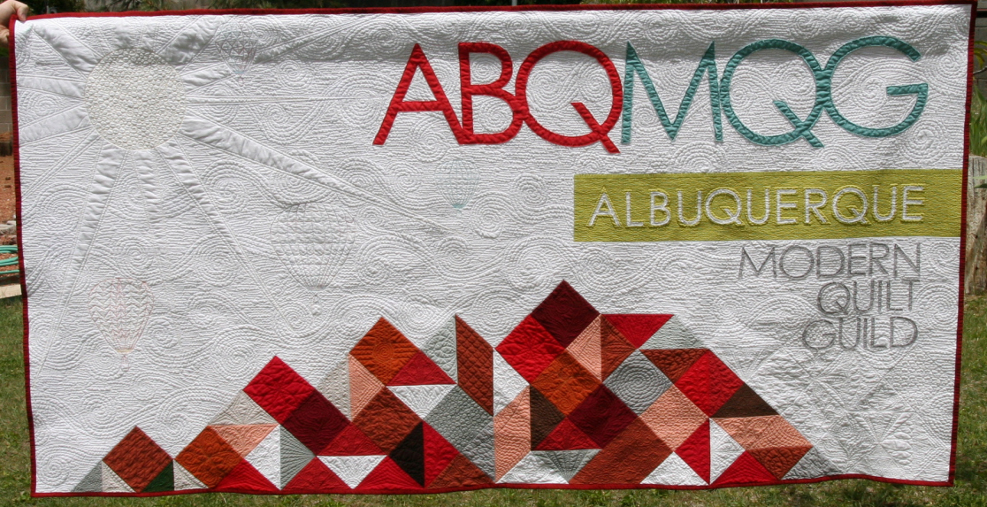 "ABQMQG  86"" x 45"" Logo designed by Bob Lowe Pieced by Lois Warwick Applique by Sally Williams & Laurie Moodie Quilting by Renee Hoffman Albuquerque MQG"
