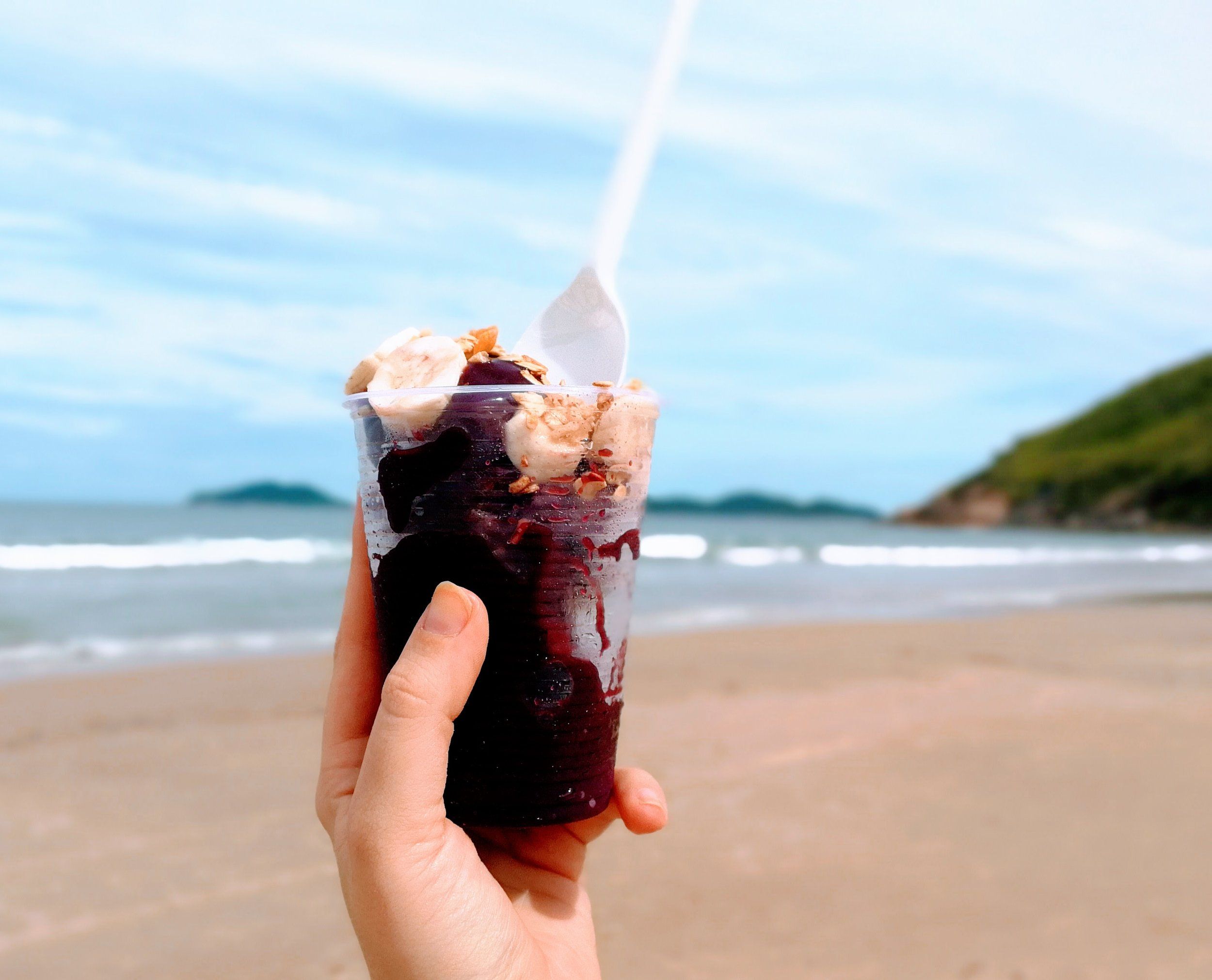 About Açaí - Açaíis a typical Brazilian snack made of frozen açaí fruit. It is served as a smoothie and is commonly topped with granola, banana, and guarani syrup.