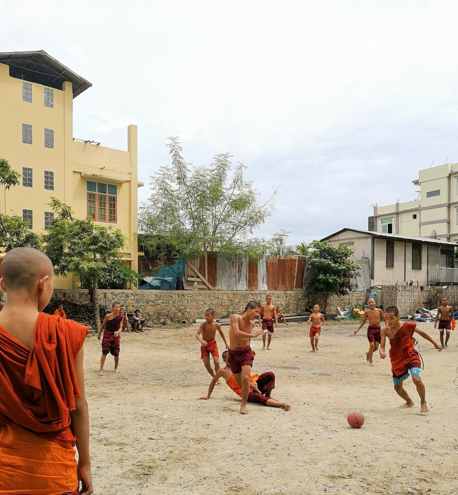 Students at a monastic school in Mandalay play football on their lunch break,