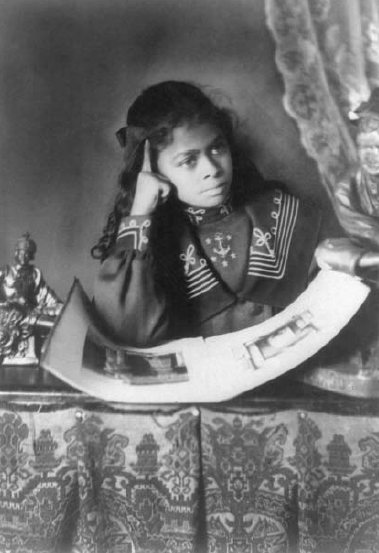"""""""African American girl, half-length portrait, with right rand to cheek, with illustrated book on table,"""" Thomas Askew, African American Photographs Assembled for 1900 Paris Exhibition, Prints and Photographs Division, Library of Congress"""
