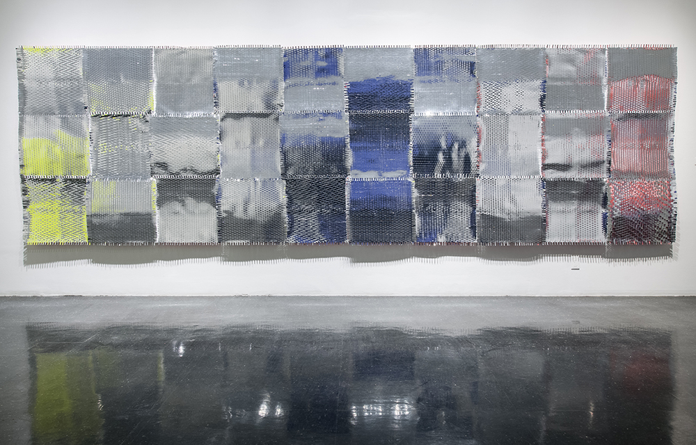 """Leigh Suggs , Trying To Exit Here , 2015                    Hand-cut and woven silver Mylar tape and paper on wooden panels, 72"""" x 240"""" x 5"""" Photo by Terry Brown"""
