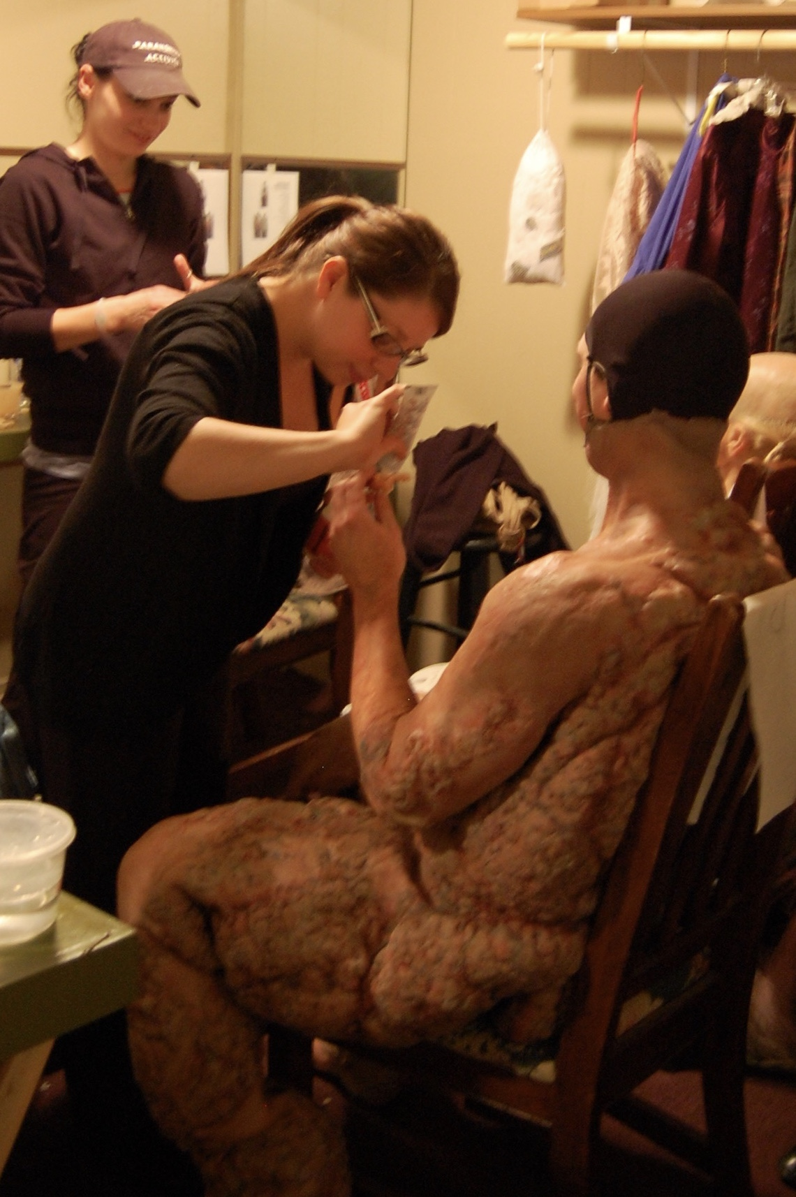 "Make-up effects artists Lee Komet and Afton Adams work on applying the body features to actor Sean Hoagland in preparation for his head and face as part of the process of physically recreating the historical ""Elephant Man"" onstage for the first time in the play's history in Lascaux Entertainment's 2011 production of  The Elephant Man , directed by John Drouillard.  Photo by Nirvana Kowlessar."