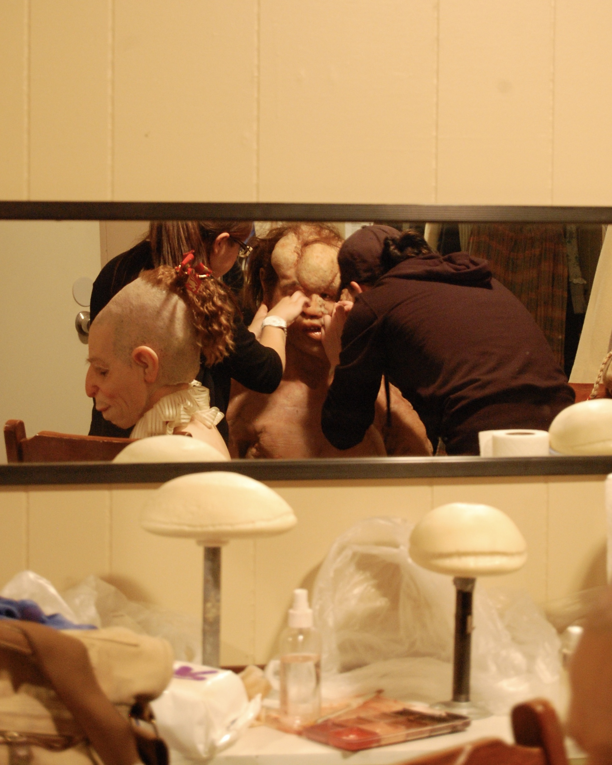 "As actor Margarita Maliagros takes a break after her own application, make-up effects artists Lee Komet and Afton Adams apply special character make-up to actor Sean Hoagland as part of the process of physically recreating the historical ""Elephant Man"" onstage for the first time in the play's history in Lascaux Entertainment's 2011 production of  The Elephant Man , directed by John Drouillard.  Photo by Nirvana Kowlessar."
