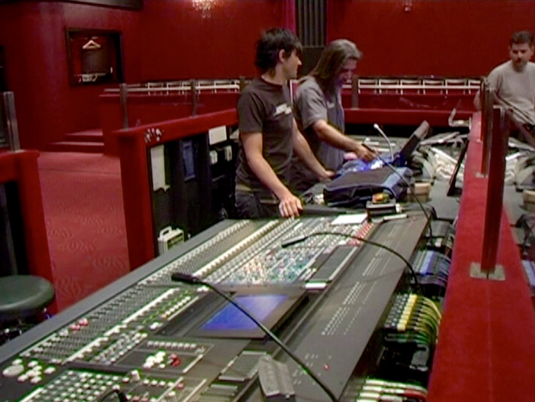 An El Rey Theatre technician works over details with sound designer Andy Fig and stage manager Christopher Beyries during load-in for GLAD & Sprint Relay's 2007 concert  Beethoven's Nightmare Live At The El Rey , produced by Bob Hiltermann, John Drouillard, and Natalie Drouillard.  Still from Worldplay, Inc.'s 2010 feature documentary,  See What I'm Saying , cinematography by Jeff Gatesman, directed by Hilari Scarl.