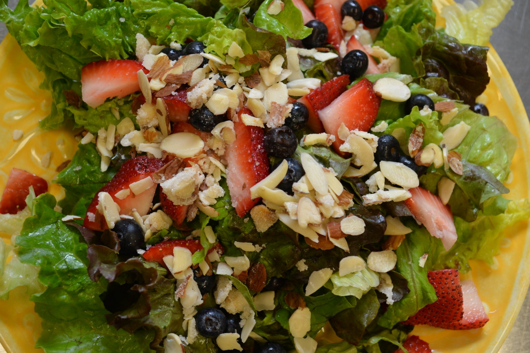 AMERICAN - Fresh red and green leafy lettuce, fresh sliced strawberries, blueberries, carmelized almonds topped off with our homemade sweet & sour red wine vinaigrette dressing