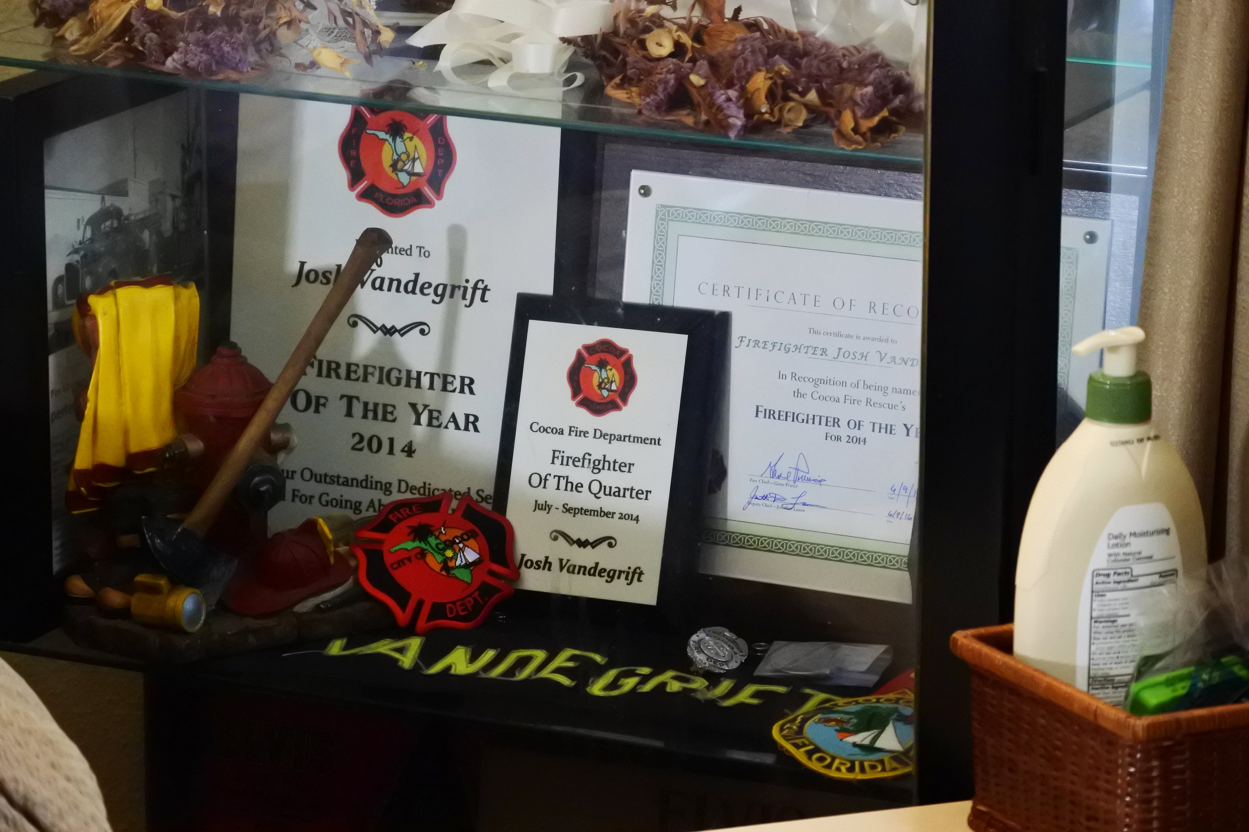 """A collection of firefighting awards and memorabilia sit on a shelf in Josh Vandegrift's home, including """"Firefighter of the Year"""" in 2014."""