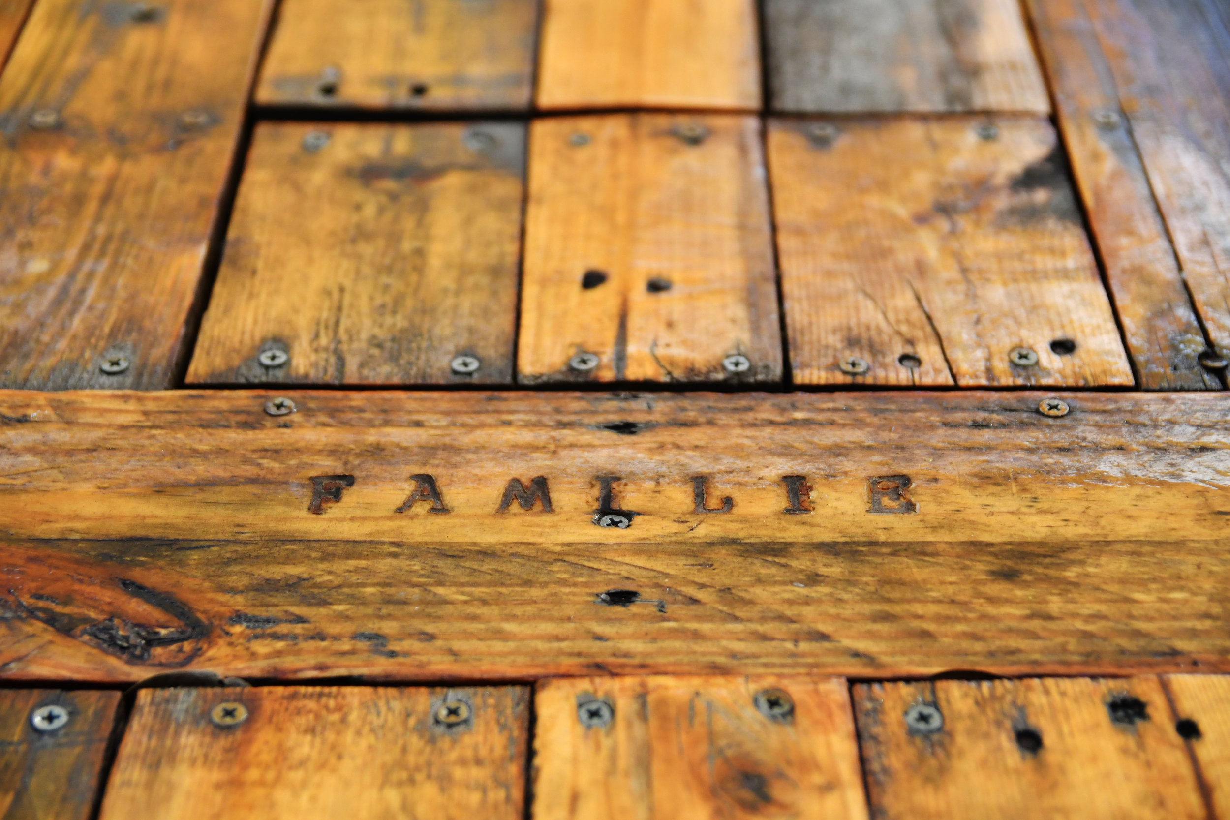 """The world """"familie,"""" which is Dutch for """"family,"""" it etched into an outside table. Vandegrift said he built the table during his time off to pass time."""