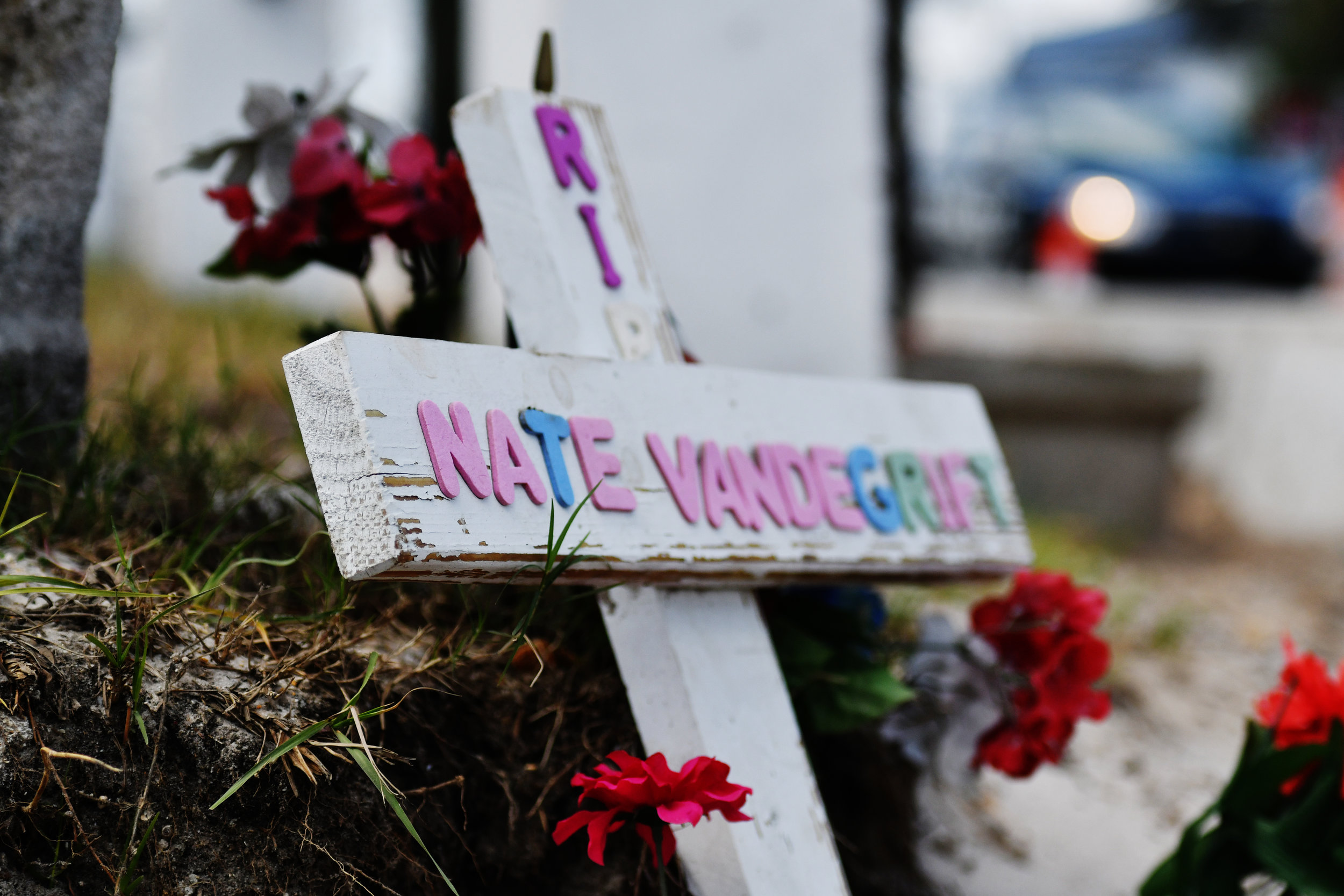 """A cross reading """"RIP NATE VANDEGRIFT"""" lies in a corner of the intersection where he passed away."""