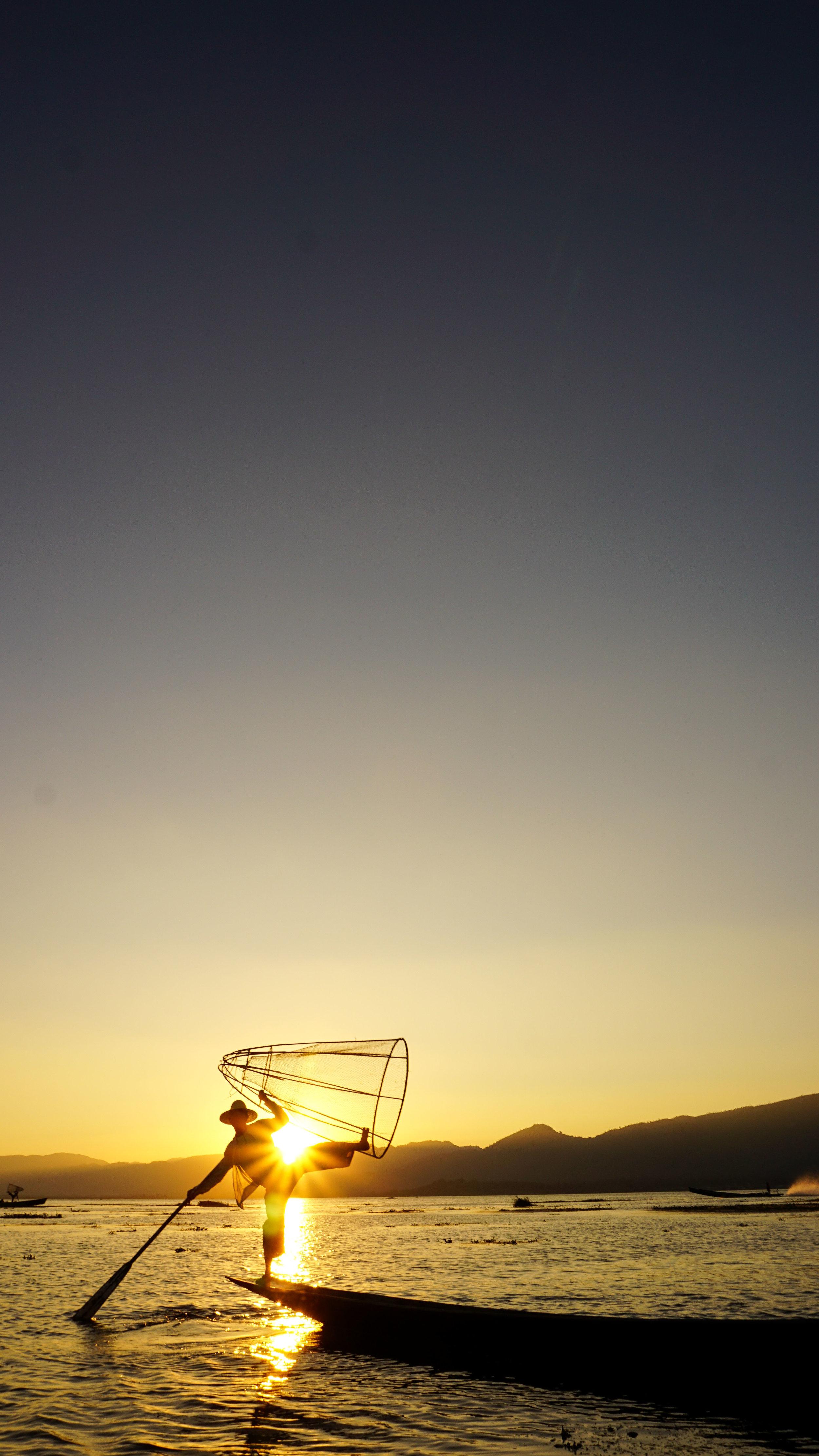 Fisherman performing at sunset on Inle Lake.