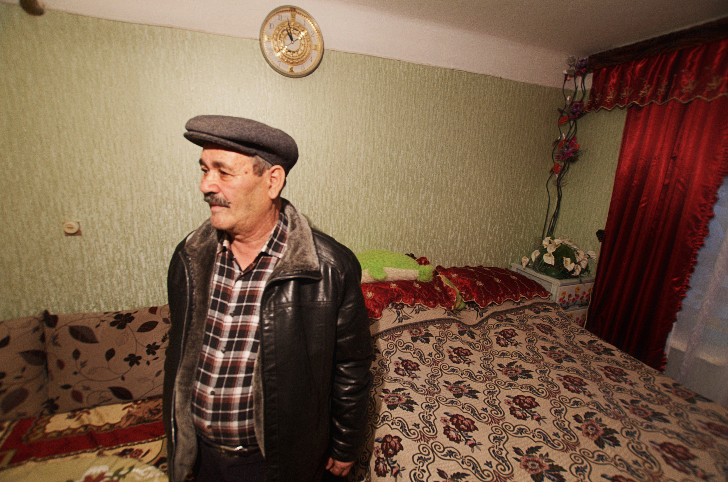 Mr Alivev stands in the room he shares with his family, Baku, Azerbaijan. 2015