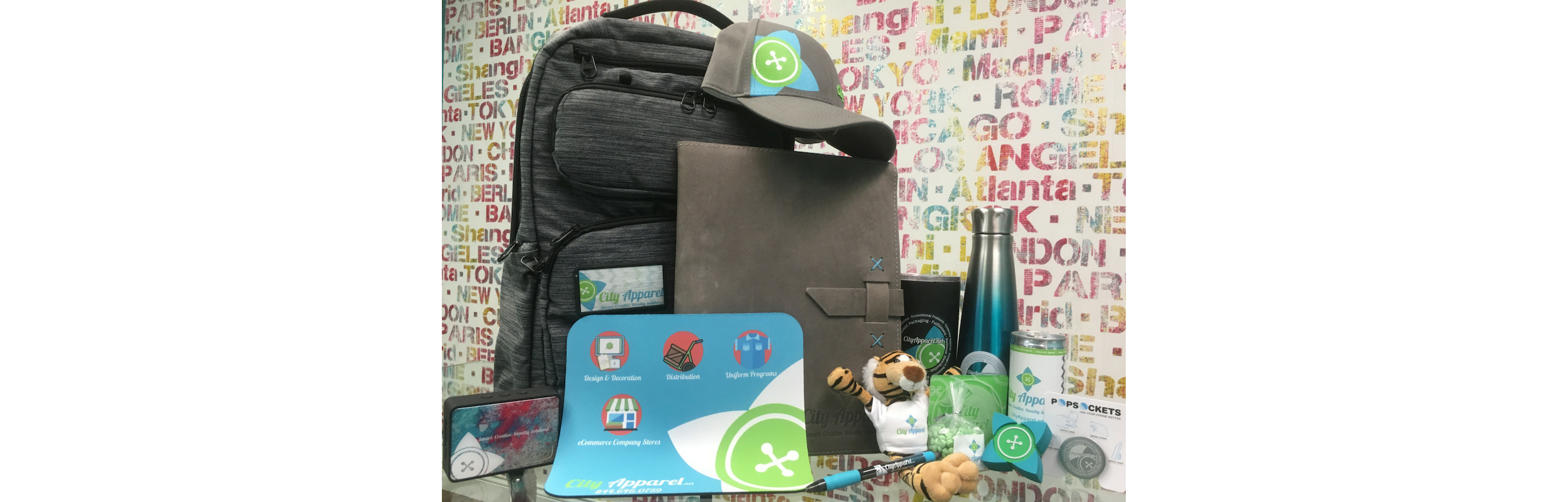 Pictured Left to Right: Bluetooth Speaker, Backpack, Mouse Pad, Portfolio, Hat, Pen, Stuffed Animal, Hot or Cold Tumbler, Coster, Stainless Steal Water bottle, Mints, USB, Energy Drink, PopSocket
