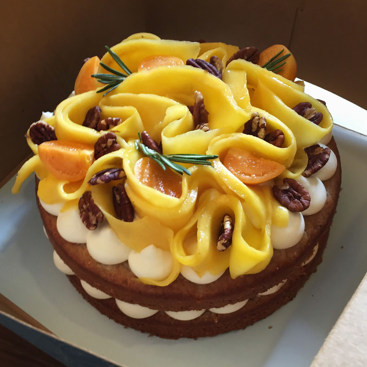 Hummingbird - Banana, pineapple, pecan cinnamon cake with cream cheese frosting. Topped with fresh mango and toasted pecan.7