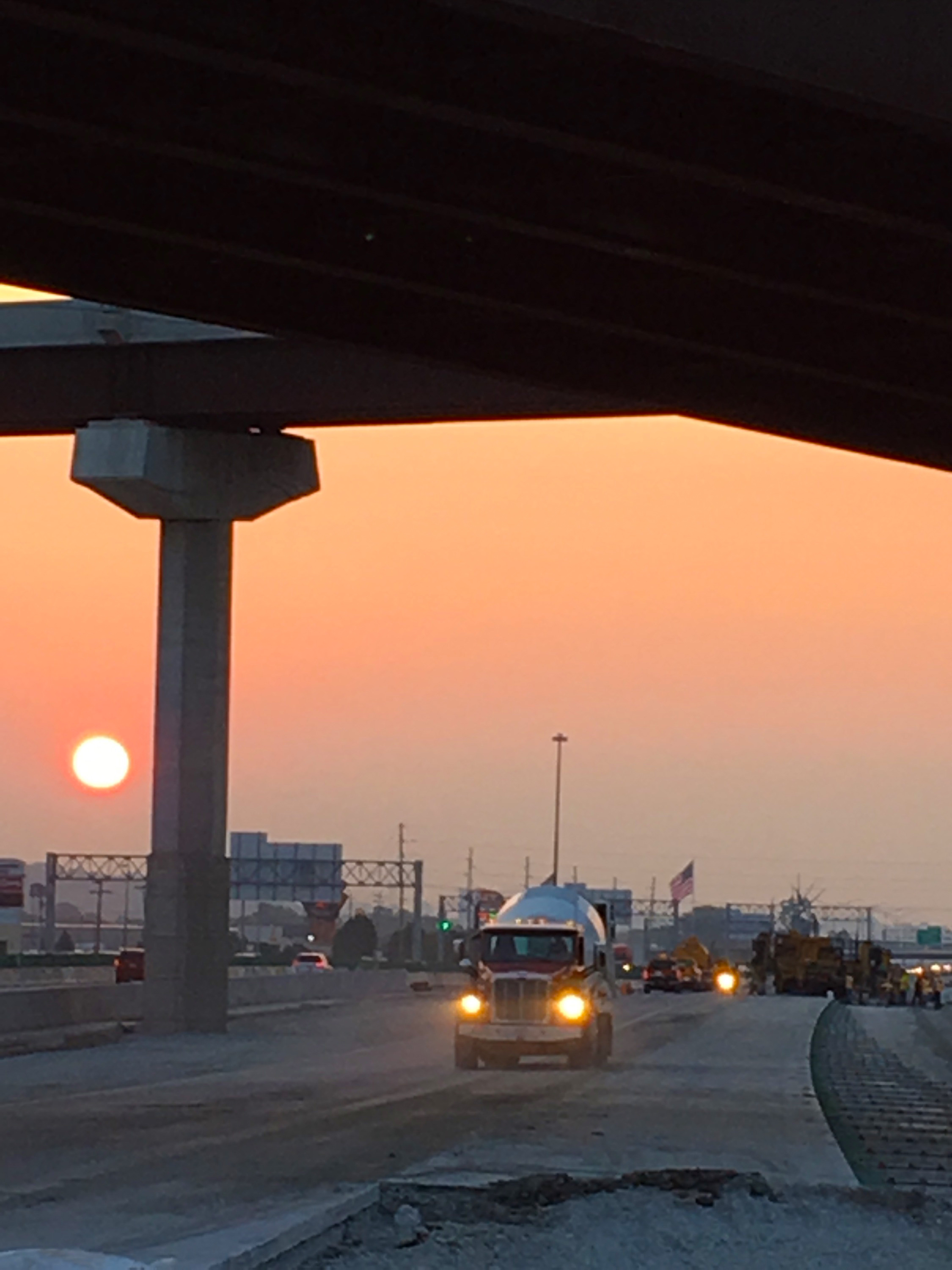 The sun rises as Ready Mixed Concrete mixer trucks haul their loads for the I-29/I-80 interchange construction on Sept. 1, 2017.