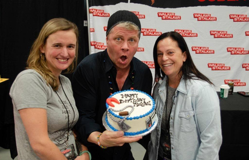 Elizabeth and her sister in law Caron presenting michael cudlitz with his birthday cake