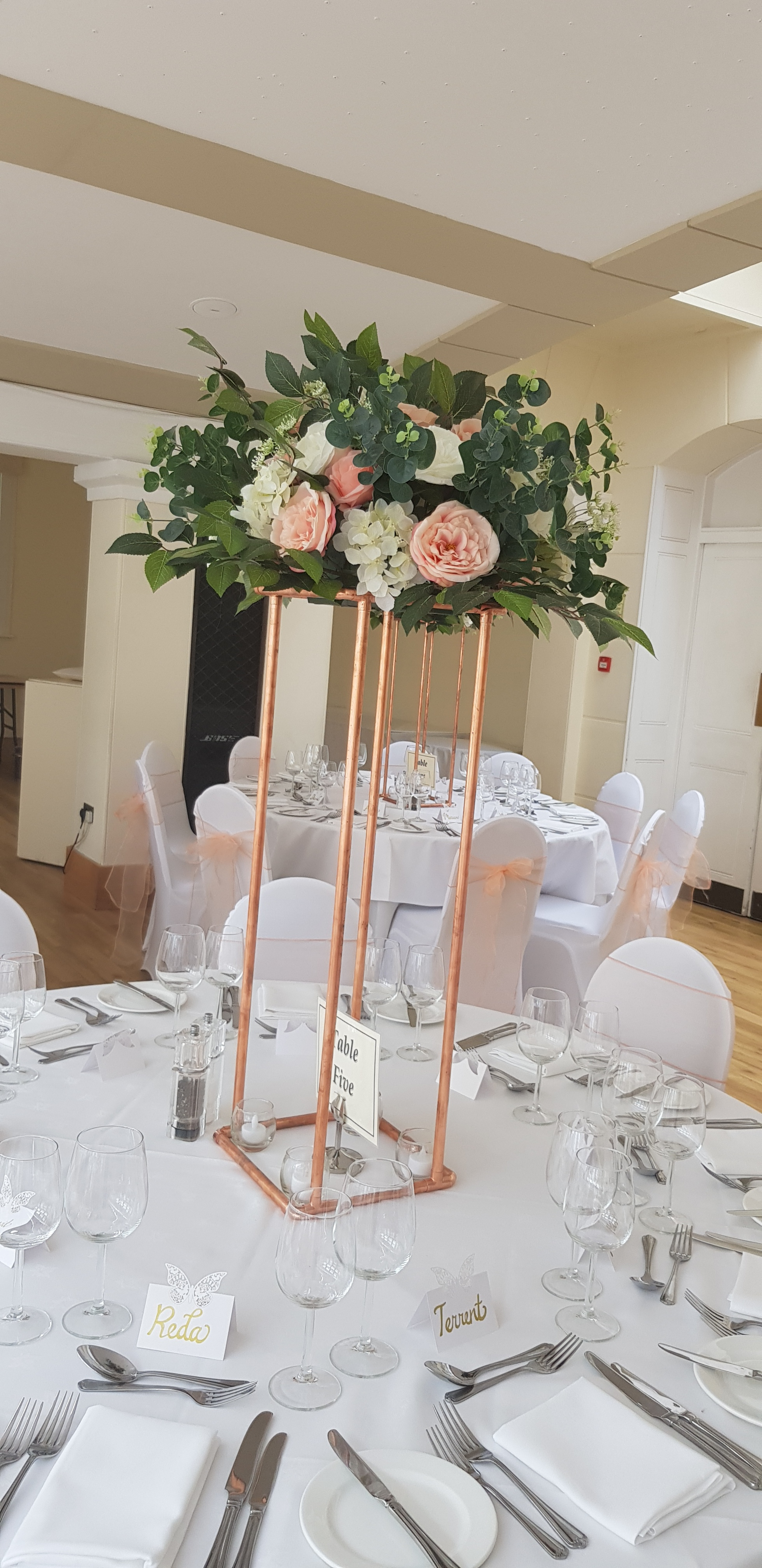 Copper plinth centrepiece - Our NEW copper plinth stands are bang on trend for this season and can be used for table centrepieces and aisle decoration. Teamed with our beautiful silk flower arrangements and hanging LED candlelit baubles, these are truly a must have for your upcoming wedding or event.Size of plinth 80cm high x 25cm wide x 25cm deep