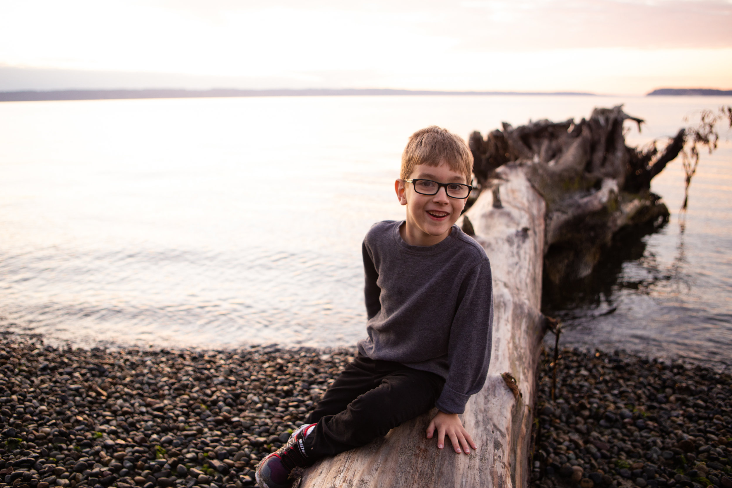 Boy smiling while sitting on log on a pebbly beach