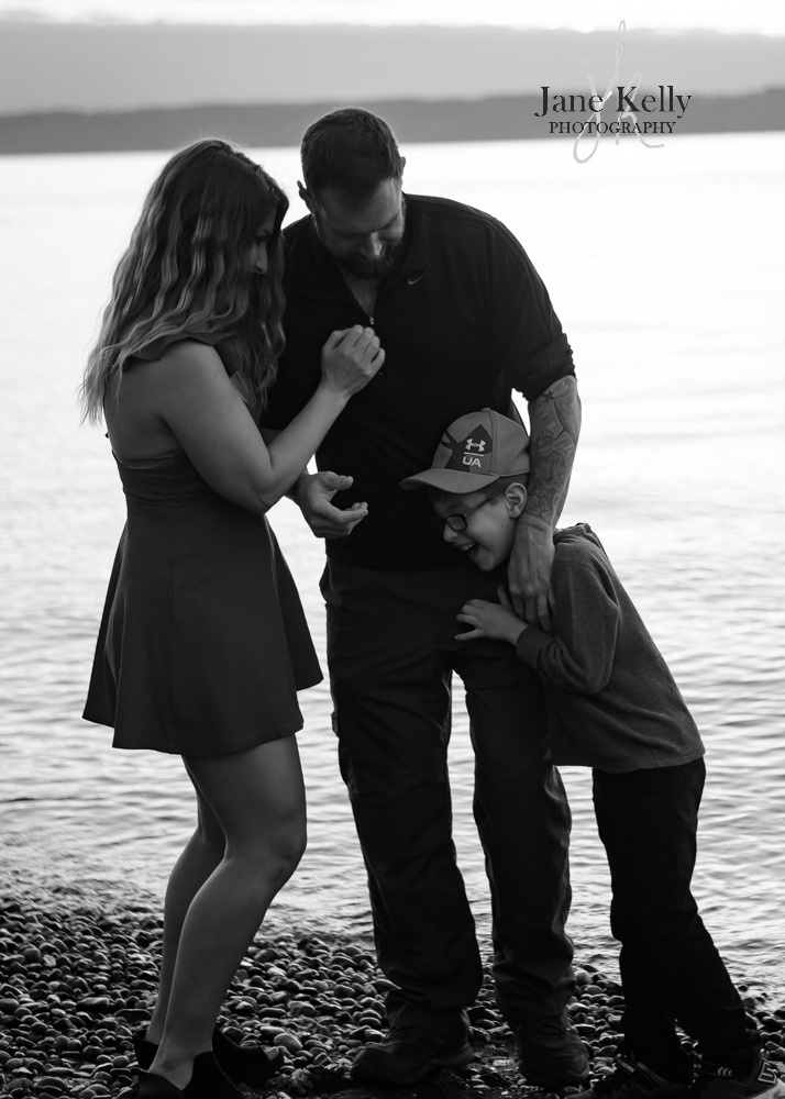 candid family laughing beachside in snohomish county