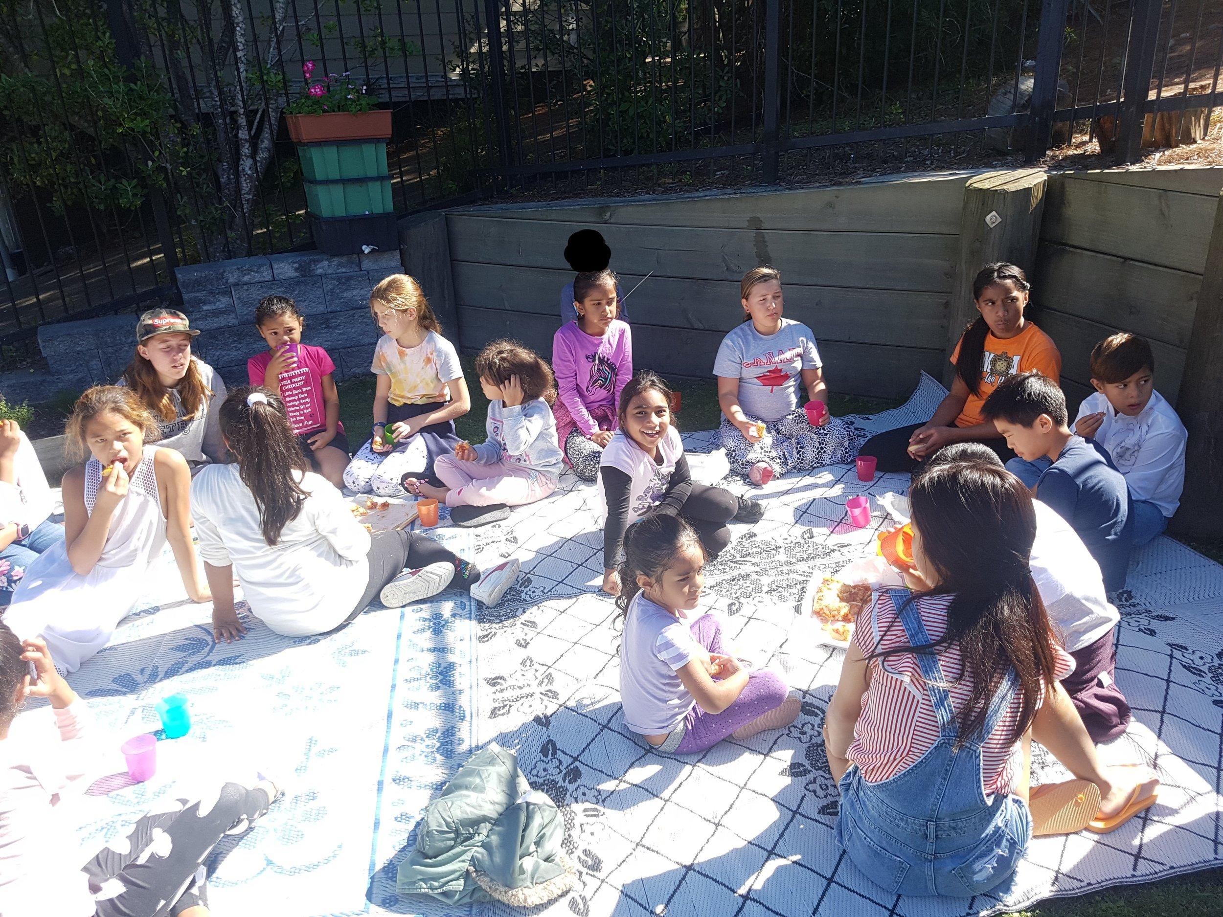 - Kids enjoying their baking inthe sun at Manutewhau Hub.
