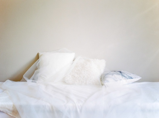 White pillows on a white bed with a light veil.
