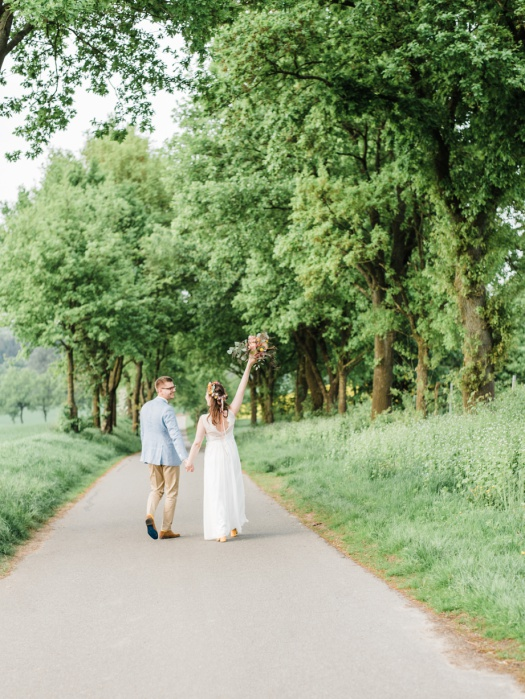Cutest bride and groom walking towards a line of trees