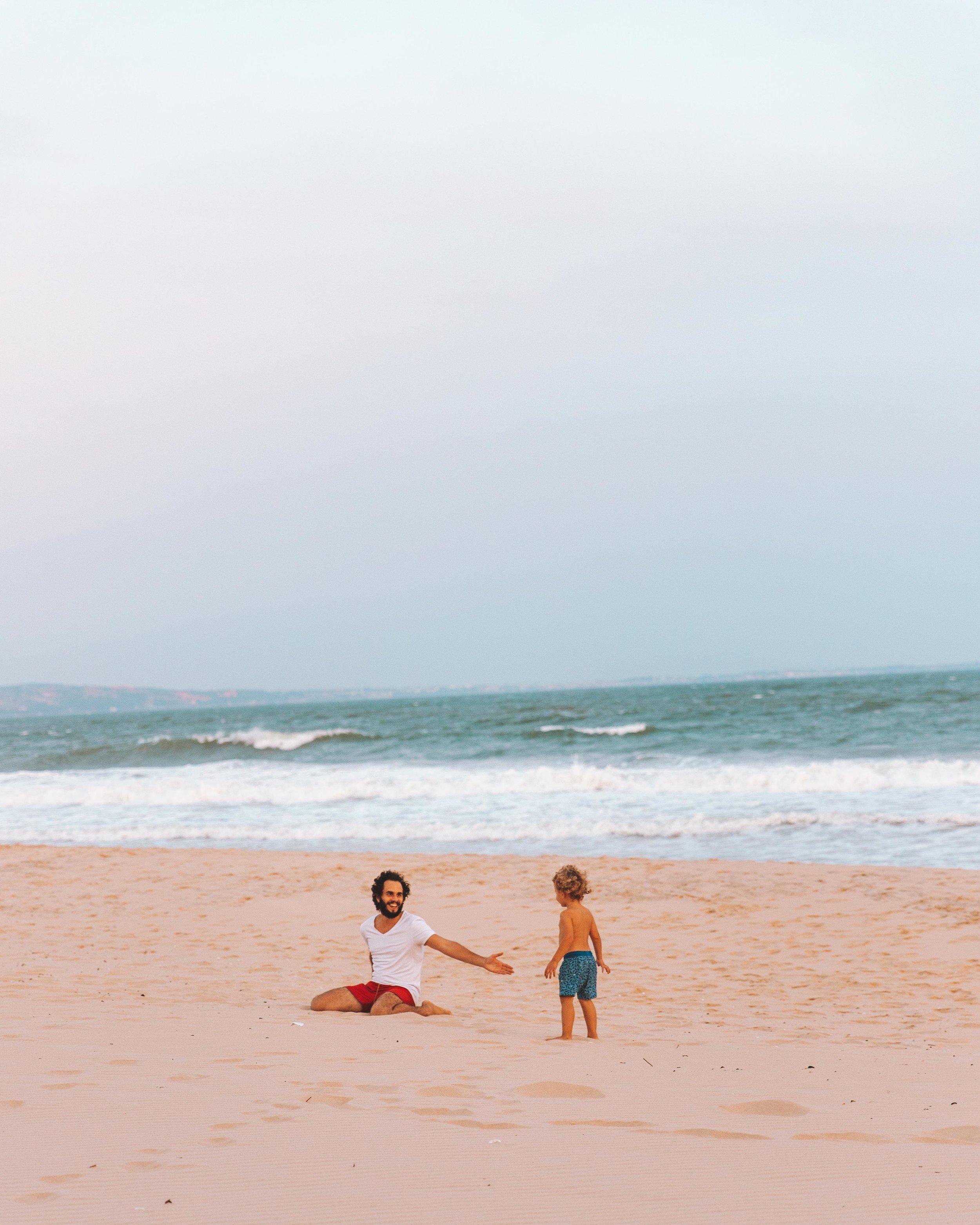 En jouant sur le sable au coucher de soleil