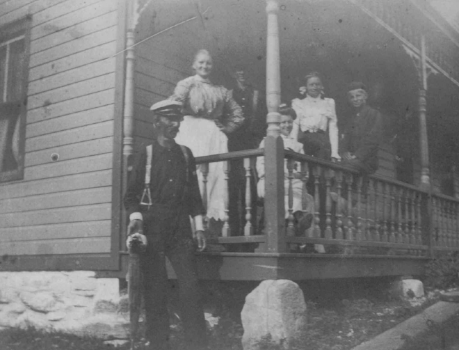 Torger is holding a fish in his right hand and standing below the porch. Anna is just behind him with Martin just visible to her left. Annie is sitting down with her legs crossed and one foot jutting through the porch spindles. To her left is Tillie and Willie is sitting on the porch railing.