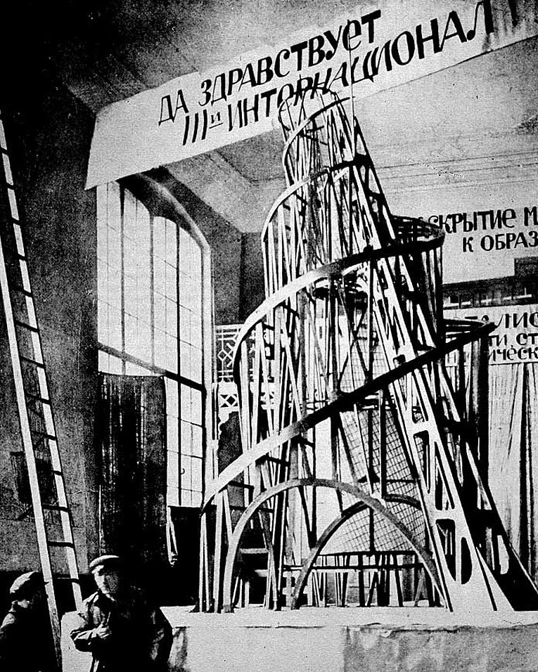 Vladimir Tatlin standing in front of a model of his tower in 1919