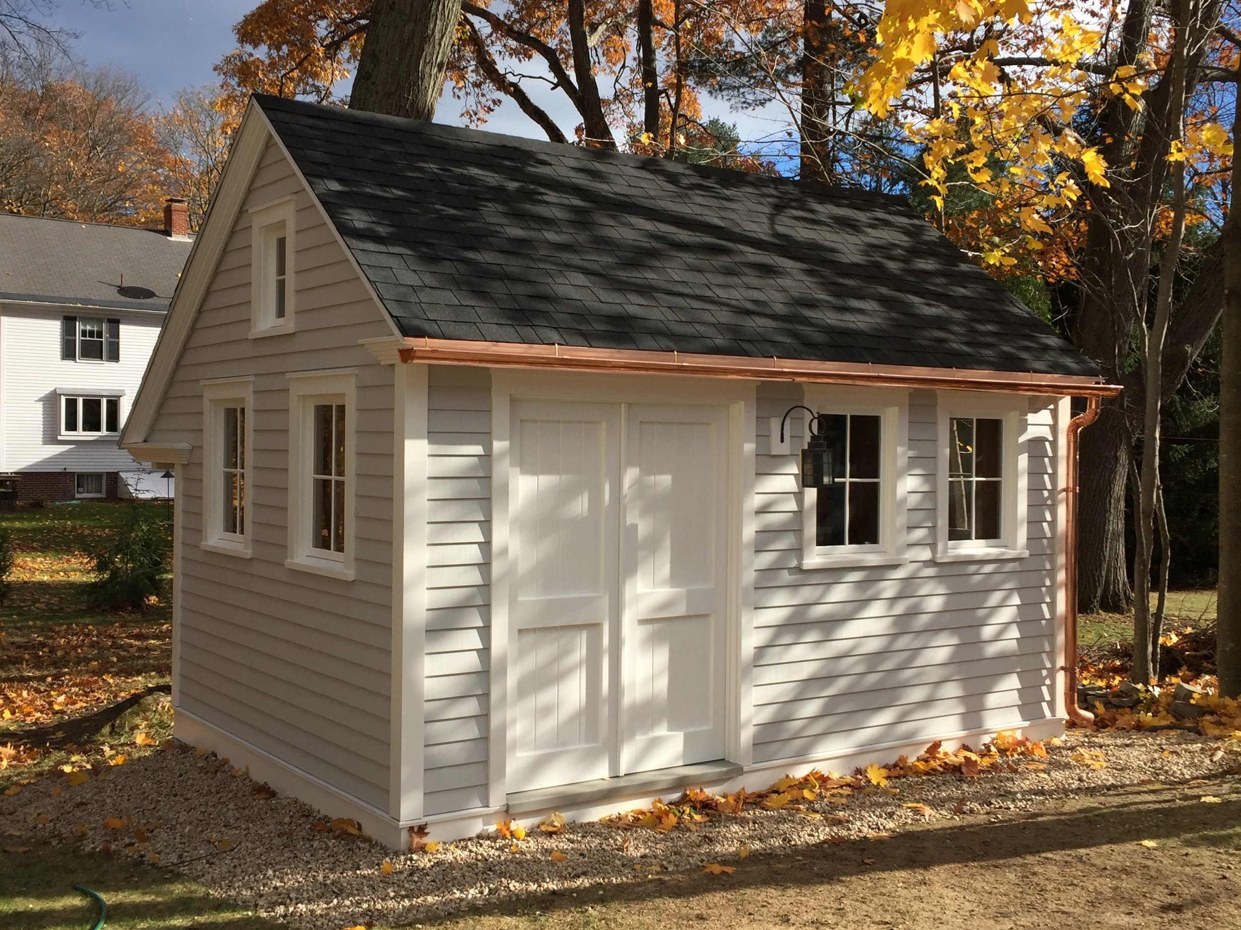 """New """"OLD"""" Garden Shed with Old Fashioned details - Custom Doors, 2 over 2 Boston sash and window frames, Classic eave returns, copper 1/2 round gutter and wood clapboards.    Maintenance free AZEK (PVC) rim band and cap @ grade."""