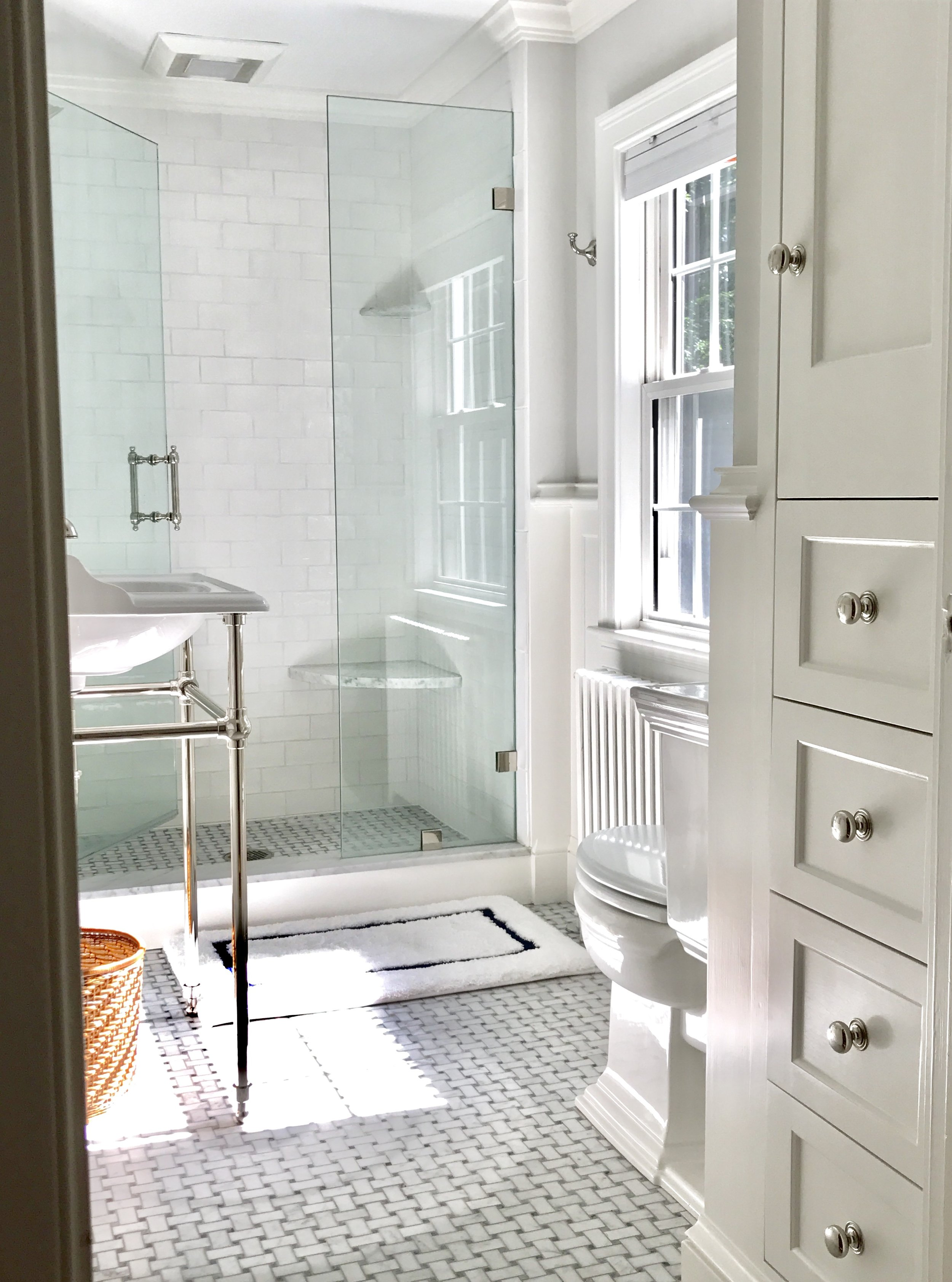 Newly renovated bathroom. A custom shower replaced the old circa 1941 bath tub. Carrara marble seat adds comfort with the ease of cleaning. Traditional marble basket weave floor tiles added a timeless look along with the new console sink and polished nickel fixtures by Perrin & Rowe.