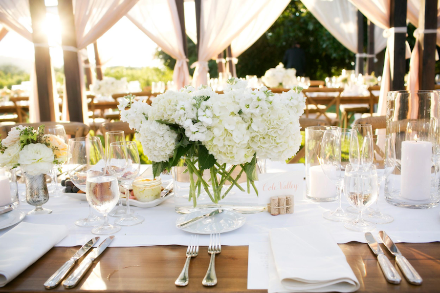 Michelle + Tyler's Wedding  Dazzling white and with an irresistible fresh feeling, Michelle and Tyler's easy breezy vineyard theme carried over beautifully in their simple sophisticated centerpieces. The couple opted for the nontraditional by having long farm tables with a light linen table runner down the center. Crystal clear vases alternated with small rustic silver vases, each holding billowing white hydrangeas that added texture to the table. In crystal clear containers, white candles rounded out the spread with simplicity and elegance. Don't you just love the light look of this centerpiece?   Floral:  Plan Décor   Furnishings + Lighting:   Bright Event Rentals   Linen:   La Tavola Fine Linen