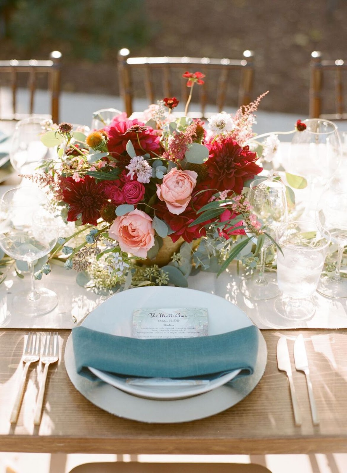Annamarie + David's Wedding  Bursting with October shades and whimsical pops of teal, this Autumnal theme was wrapped up beautifully by their blossoming centerpieces. Bedded by a neutral linen table runner that stretched along the farm king-style table, a cool blueish-green garland draped down the center with ease. To bring in splashes of Autumn color, textured floral arrangements of blooms in burgundy, fuschia, and peach with pops of succulents were placed along the center, and scattered in between with lush pomegranates. A beautiful Autumn centerpiece expression, indeed! Florals:   Loop Flowers   Rentals:  Bright Event Rentals  Paper Goods: Etsy