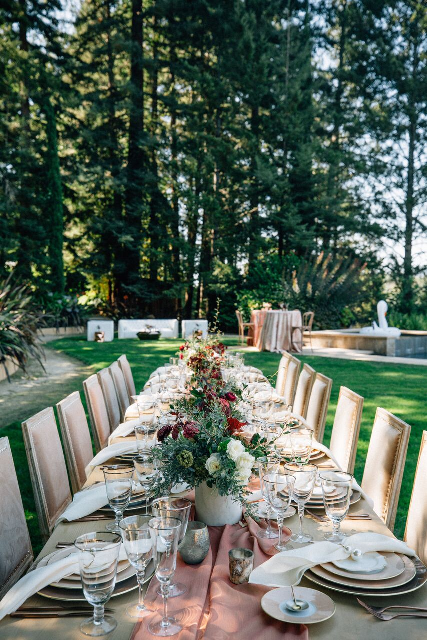 Calistoga Wedding   Wine colors, soft pinks, and earthy greens - oh my! The centerpieces from the Calistoga styled shoot carried a sense of bohemian romance and we just can't get enough. A tousled pink table runner set the tone, as bouquets big and small alternated down the center. Small candles in rustic metallic tone vases dotted the table with shimmer and shine, while the leafy greens and wine red blooms tied the whole table setting together.