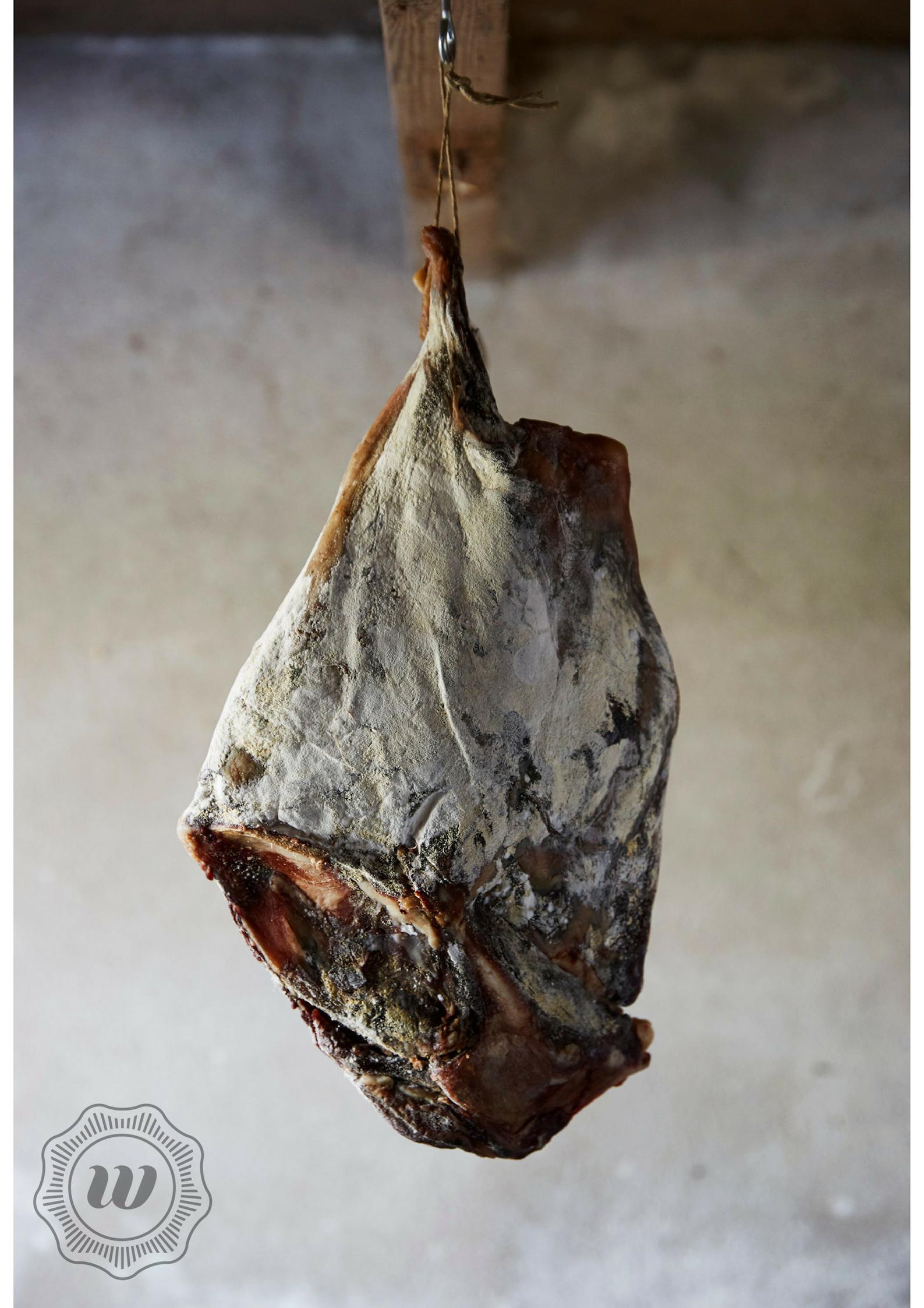 GEDROOGDE HAM - Voor de ham wordt gebruik gemaakt van de achterbout. Eerst wordt de ham gepekeld. Daarna gaat hij in onze rijpingscel voor het optimale resultaat. Door continue sturing van zowel temperatuur als luchtvochtigheid kan de ham rustig en gecontroleerd drogen en rijpen. Onze hammen maken wij van wild zwijn en hert.