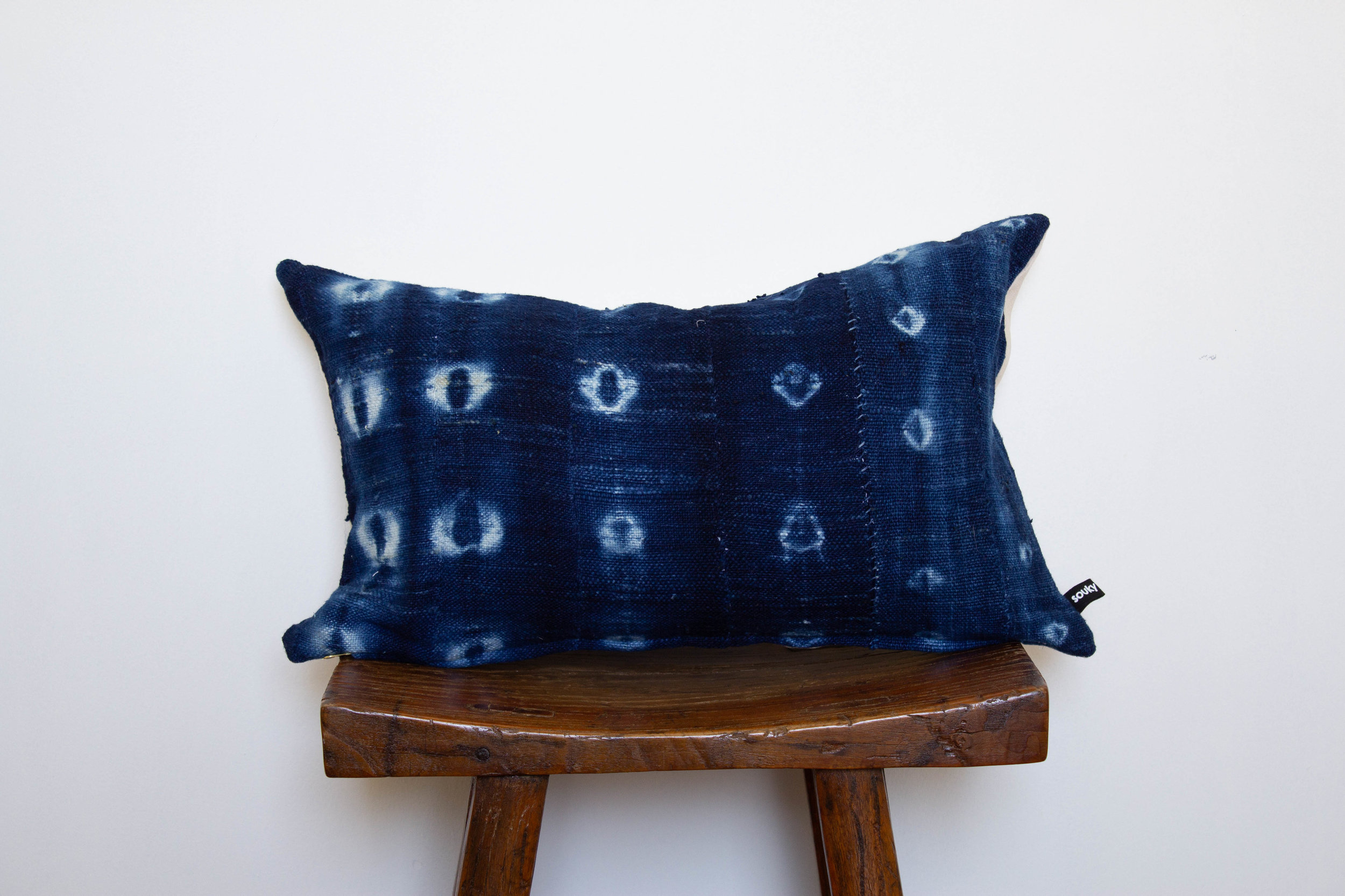 Sabine- 2 available    350 RMB  Pillow cover is made from dyed indigo, African mud-cloth sourced from Ghana  Size: Roughly 52x32 cm  Pillow back is made from a neutral cotton/linen blend  Zipper on bottom of pillow  Down insert included  Hand wash or spot clean recommended