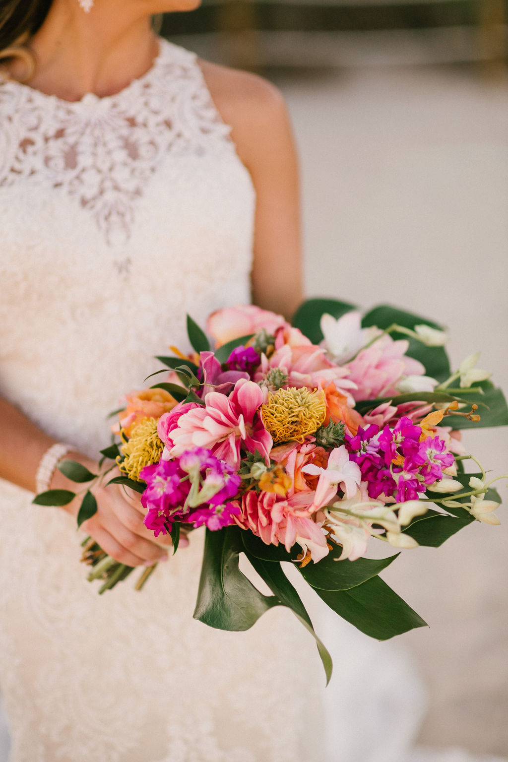 Our bride's bouquet by  Beautiful Kreations  is delightfully scattered with protea, larkspur, and alpinia with a split leaf philodendron as the base.