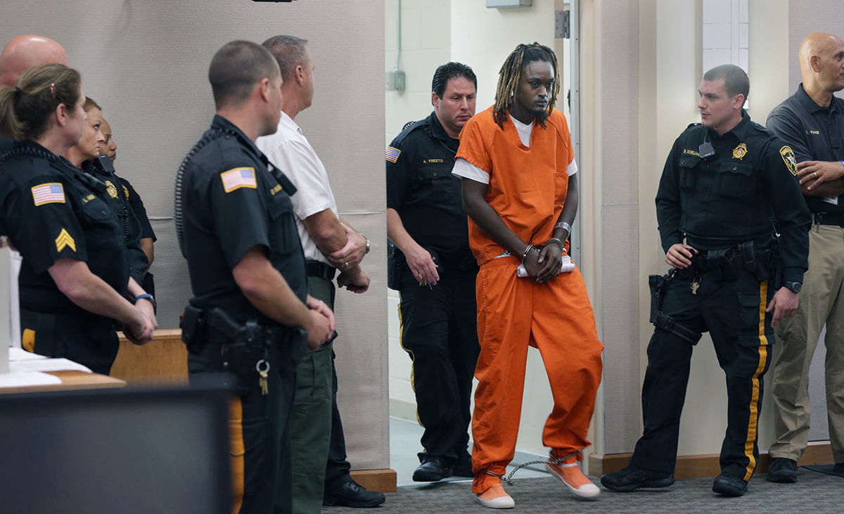 Do jurors think this man looks guilty because of the way he is dressed and who is surrounding him?