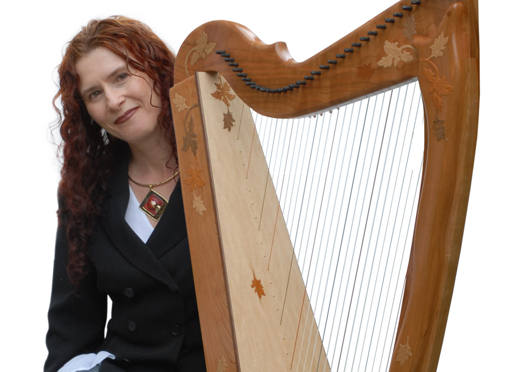 Internationally famous Irish Harp Champion Máire Ní Chathasaigh and her cherry A to A Rees Aberdeen Meadows Harp with optional Autumn Leaves ornamentation.
